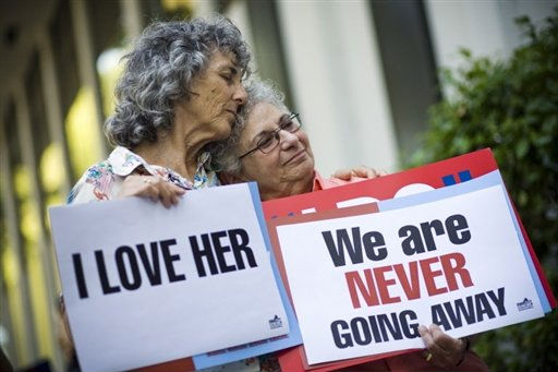Lesbian couple with pro-marriage equality signs